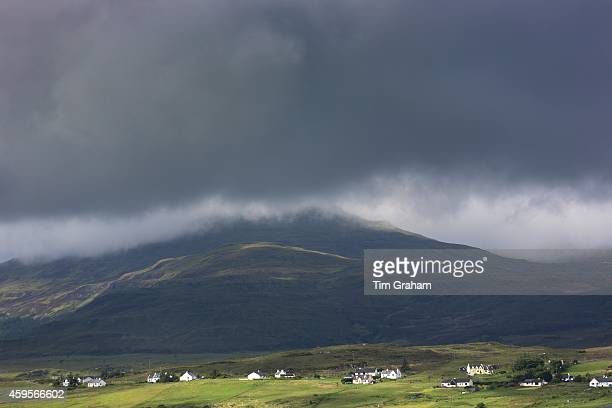 White croft cottages nestled under a mountain and grey clouds near Harlosh on the Isle of Skye Western Isles of Scotland UK