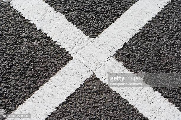 White cross shape on tarmac road