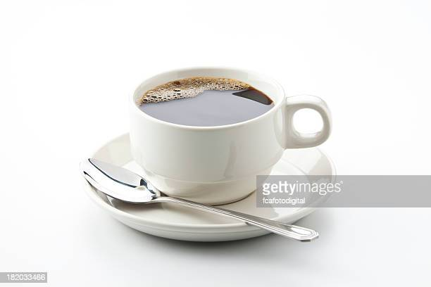 White cup full of black coffee with a spoon