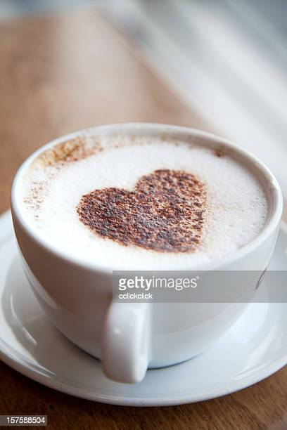 A white cup of cappuccino with a heart in the middle
