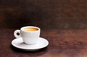 White cup of espresso coffee on background