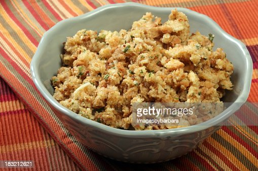 White decorative bowl of stuffing on a striped tablecloth
