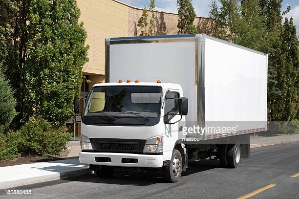 White delivery truck parked on road with trees