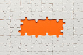 White details of puzzle on orange background and place for inscription.