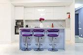 Modern white kitchen interior with purple bar chairs, minimalistic clean design