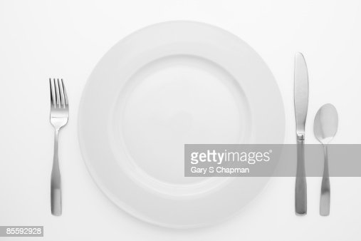 White dinner plate and silverware on white : Stock Photo