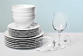 Stack of commercial plates and bowls on table beside two wine glasses