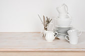 White dishware and cutlery on wooden table with copy space