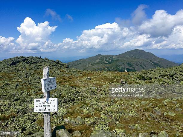 White Distance Sign On Rocky Landscape Against Sky At Mount Adams