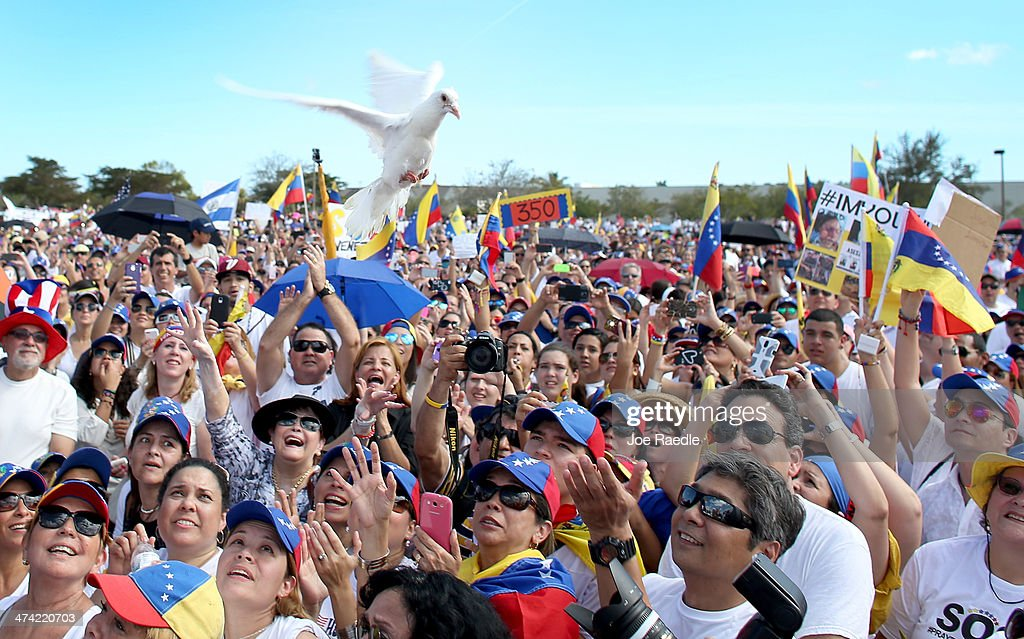 A white dove flies over the crowd after being released as Venezuelans and their supporters show their support with the anti-government protests in Venezuela on February 22, 2014 in Doral, Florida. In Venezuela, protests over the past couple of weeks have resulted in violence as government opponents and supporters have faced off in the streets.