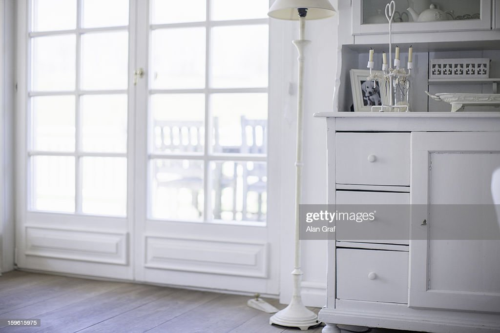 White drawers and lamp by windows : Stock Photo