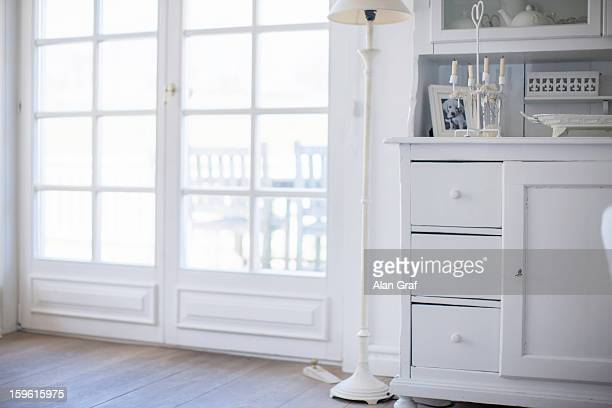 White drawers and lamp by windows