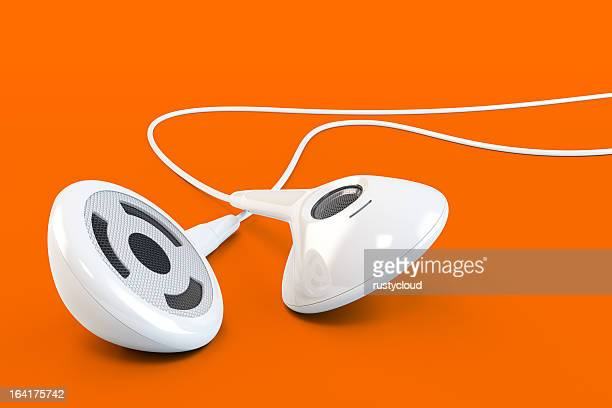 White earphones against orange background