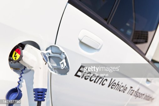 White Electric Car is being charged Outdoor : Stock Photo