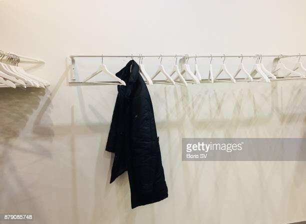 White empty hangers with one black coat
