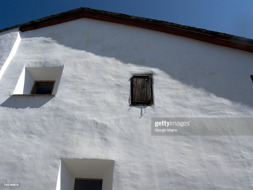 White facade of an old building with three windows