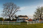 White farmhouse behind white fence in rural Illinois