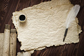 Old paper, scroll and quill pen on wooden paper with copy space