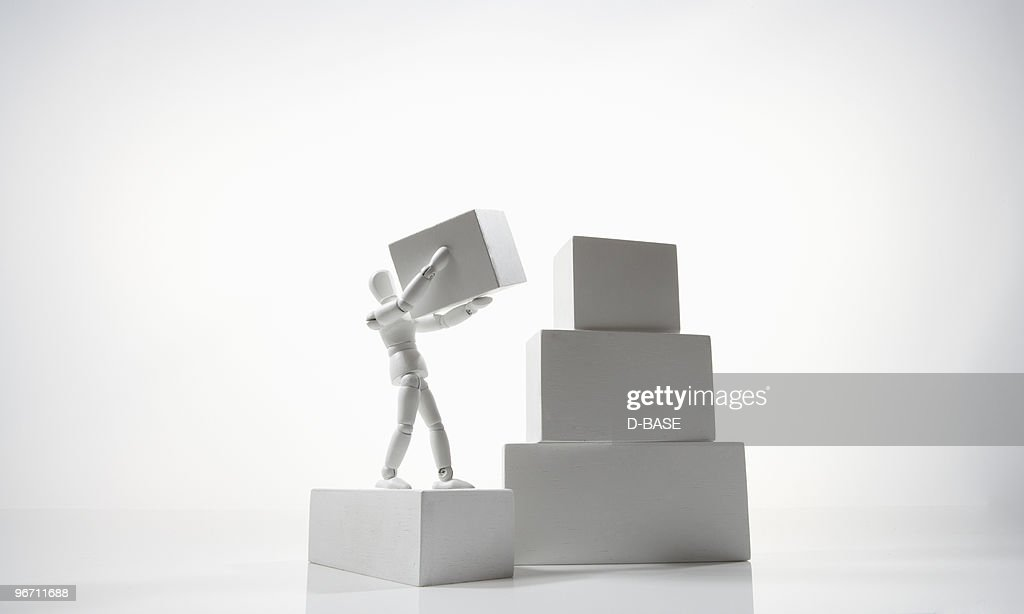 white figure carrying a box to the top : Stock Photo