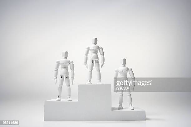 white figures standing on winners podium.