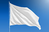 White flag blowing in the wind in front of a clear blue sky