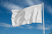 blank white flying flag on a clear sky