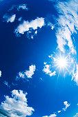 White fluffy clouds, the sun and blue skies taken wish fisheye