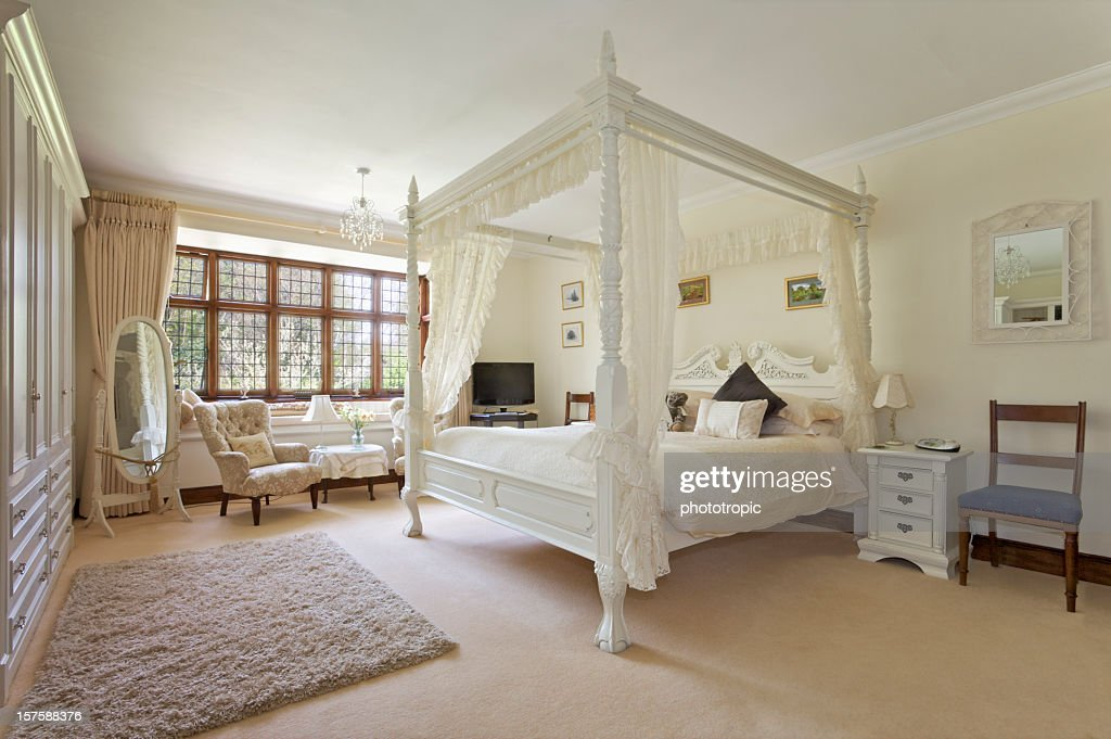 white fourposter bed in large bedroom