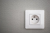 White french electrical outlet/plug on a wall.