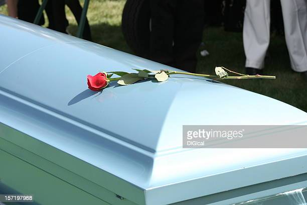 White funeral casket with a single red rode placed on top