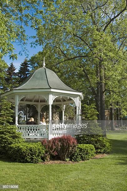 Blanc kiosque dans le parc paysager luxuriant de printemps