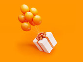 White gift box tied with orange colored ribbon is carried away by orange colored balloons on orange background.  Horizontal composition with copy space, Great use for Christmas and Valentine's Day rel