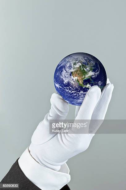 White gloved hand presenting globe.