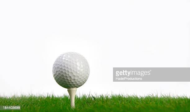 White Golf Ball and tee on green grass