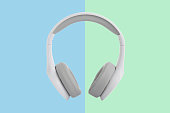 White headphones on colored background.