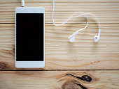 White headphones with smartphones on the wood table and free space for text and logo or symbols in the technology, communication and entertainment concept.