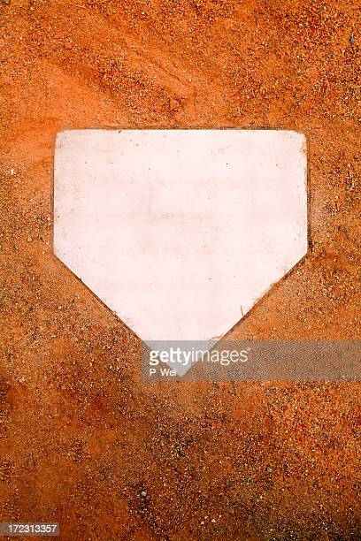White home plate set in orange sand