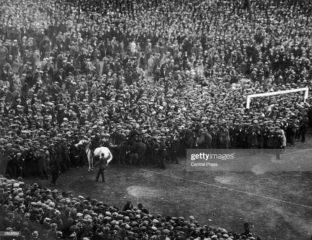 Mounted policemen control the crowds overflowing onto the pitch before the FA Cup Final between West Ham United and Bolton Wanderers at Wembley...