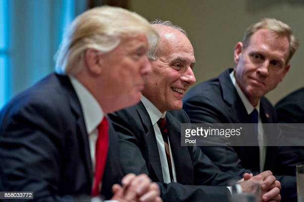 White House chief of staff John Kelly smiles at a briefing as US President Donald Trump speaks at a briefing with senior military leaders in the...