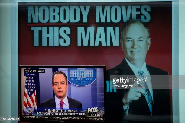 White House Chief of Staff Reince Priebus is interviewed on 'Fox And Friends' seen on a monitor outside of the Fox News studios on February 17 2017...