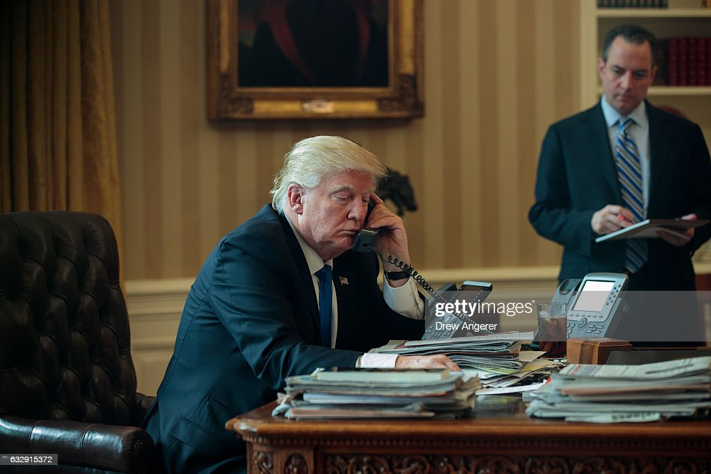 White House Chief of Staff Reince Priebus (R) looks on as President Donald Trump speaks on the phone with Russian President Vladimir Putin in the Oval Office of the White House, January 28, 2017 in Washington, DC. On Saturday, President Trump is making several phone calls with world leaders from Japan, Germany, Russia, France and Australia.
