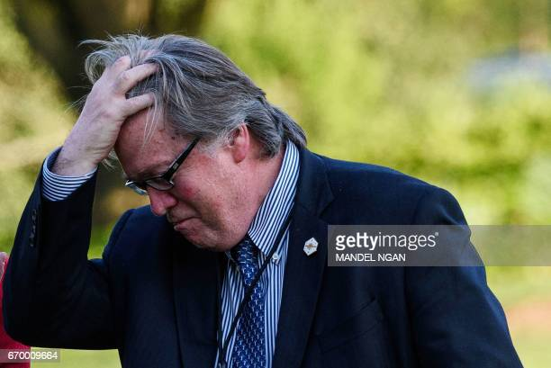 White House Chief Strategist Stephen Bannon walks across the South Lawn upon return to the White House with US President Donald Trump in Washington...