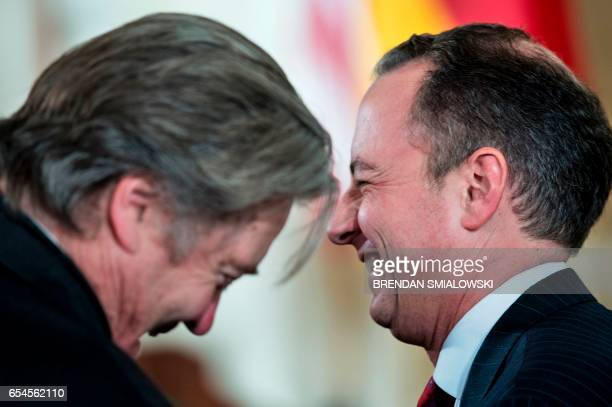 White House Chief Strategist Steve Bannon and White House Chief of Staff Reince Priebus laugh before a press conference with US President Donald...
