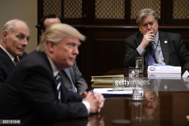 White House Chief Strategist Steve Bannon listens to US President Donald Trump at the beginning of a meeting with government cyber security experts...