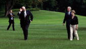 White House Deputy Chief of Staff Joe Hagin waves as US President George W Bush and First Lady Laura Bush look on after they returned to the White...