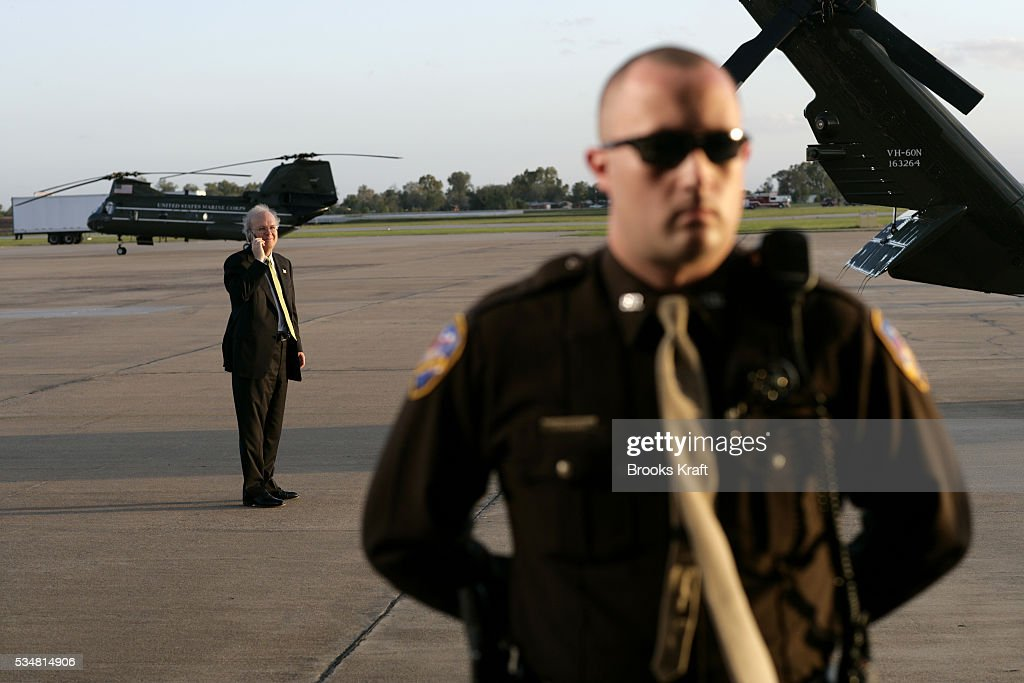 White House Deputy Chief of Staff Karl Rove talks on a mobile phone behind Marine One while President George W Bush speaks at a campaign rally in an...