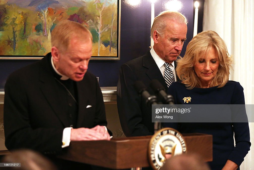 White House Military Chaplain Stanley Fornea (L) leads to say a prayer for the meal as U.S. Vice President Joseph Biden (2nd R) and his wife Jill Biden (R) bow their heads during an early Thanksgiving Dinner November 19, 2012 at the Vice President's residence at the Naval Observatory in Washington, DC. The Bidens continued a tradition to host the 4th annual dinner for Wounded Warriors being treated at the Walter Reed National Military Medical Center and their families who will not be able to leave the DC area to be with family for the holiday.