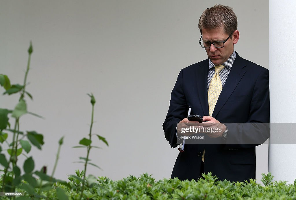 White House Press Secretary Jay Carney looks at his phone during a news conference with U.S. President Barack Obama and Prime Minister Erdogan of Turkey (not shown), in the Rose Garden at the White House, May 16, 2013 in Washington, DC. President Obama answered questions on the IRS Justice Department invesigation and talked about the situation with Syria.