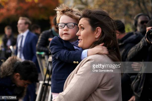 White House Press Secretary Sarah Huckabee Sanders holds her son Huck as they watch the Marine One helicopter lift off from the South Lawn with US...