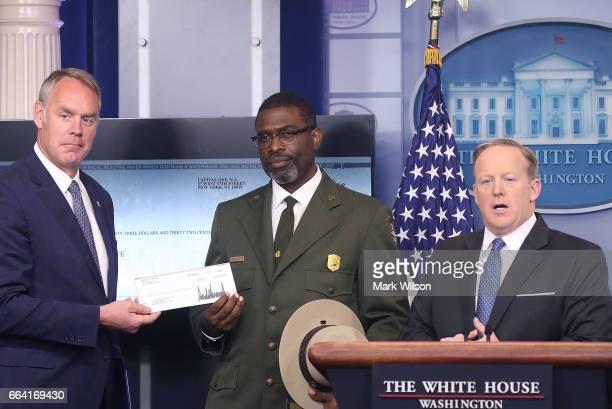 White House press secretary Sean Spicer gave Interior Secretary Ryan Zinke the first quarter check of US President Donald Trump's salary which he...